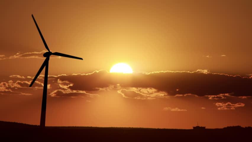Backlit wind turbine at sunset - HD stock footage clip