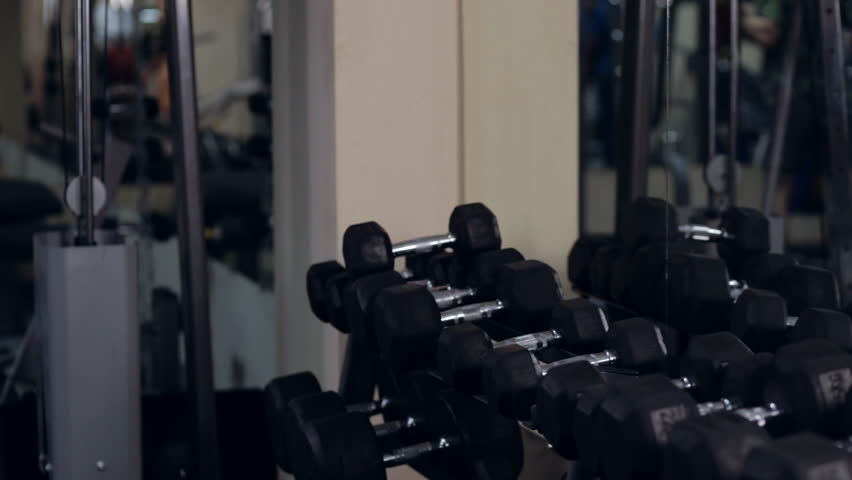 Young fit beautiful girl in gym. Graded. Taking dumbbells - HD stock footage clip