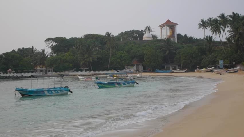 Calm sea with a three sway boats at sunrise, Sri lanka, Unawatuna beach - HD stock video clip