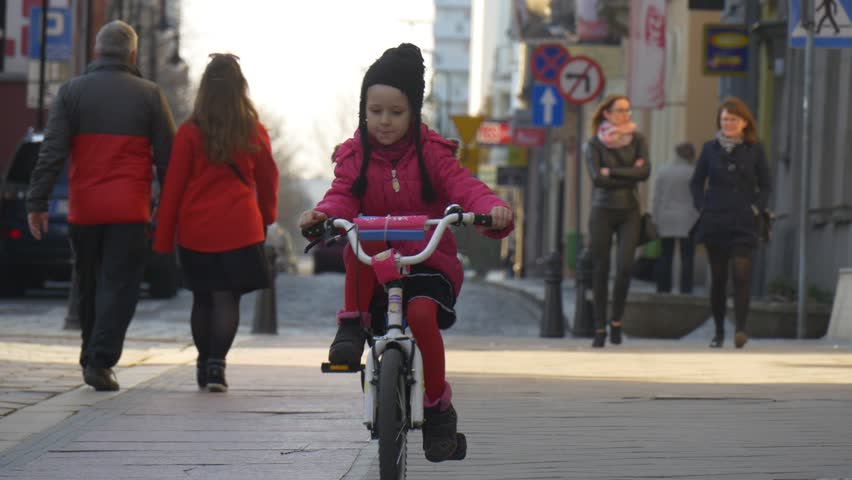 Opole/poland - Mar 28 2016: Kid, Little Girl is Riding the Bike by City Sqare in Opole, Poland, City Day. Child is Riding Toward Camera Among Crowd of People. Blonde Girl in a Red Jacket, Black Hat - 4K stock video clip