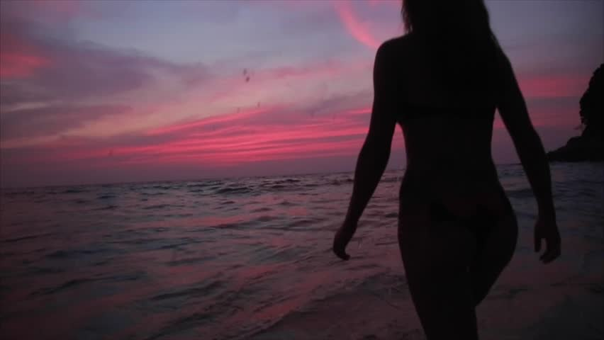 Mysterious silhouette sexy girl at beach during sunset