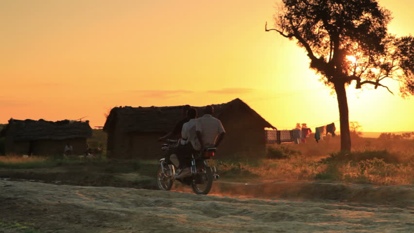 Three people riding past on a motorcycle at sunset in Kenya, Africa.