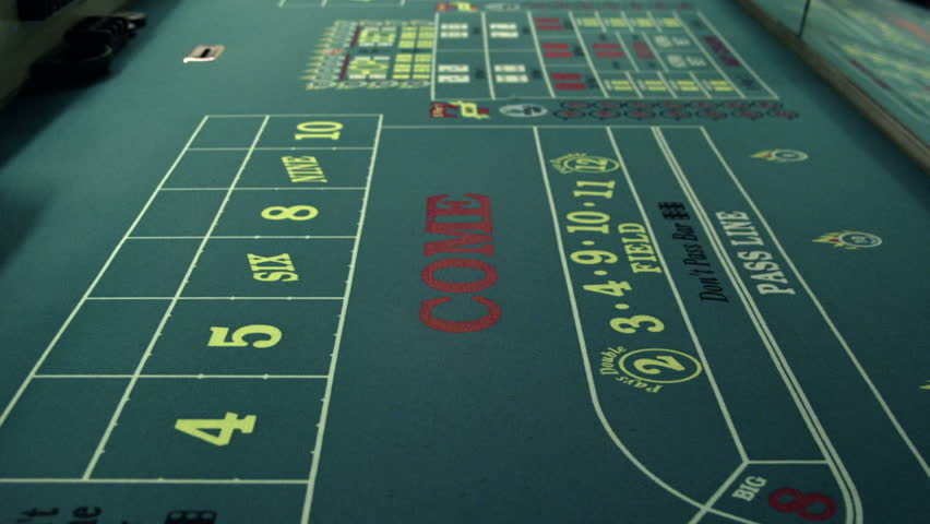 Dice rolling across a craps table. | Shutterstock HD Video #1701799