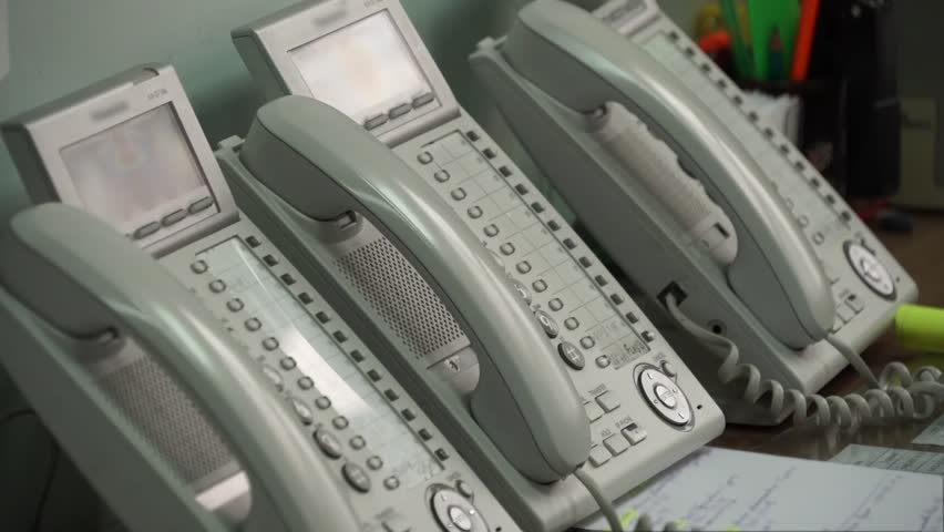 Hand picks up the phone and dials a number on the phone. - HD stock video clip