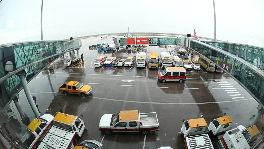CHINA - JUNE 28, 2009: Trucks and vans drive across rainy airport runway on June 28, 2009 in China. - HD stock footage clip