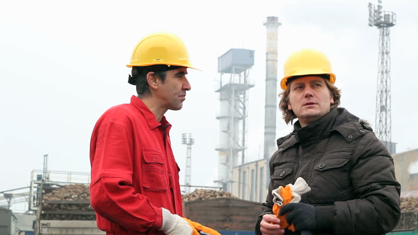 Two Factory Workers Talking Face To Face Outside The ...