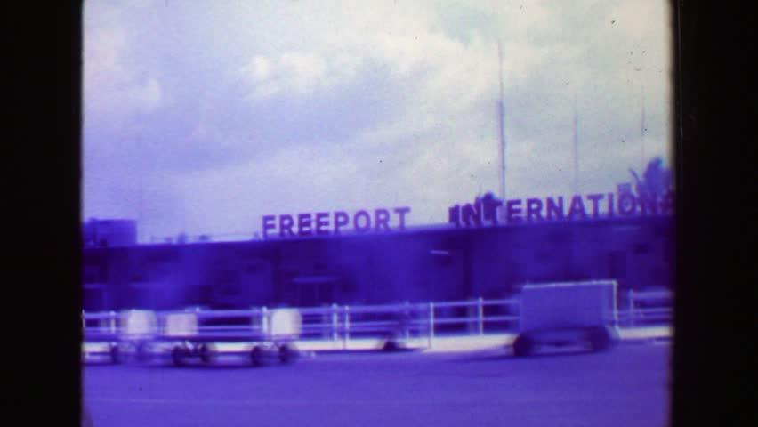 FREEPORT, BAHAMAS 1969: Freeport International Airport business man carries overnight suit luggage.
