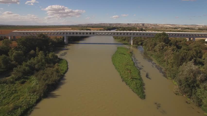 Side view of train bridge over ebro river, approaching camera, slow shutter speed in 4K