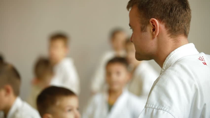 Martial arts instructor training children in gym - HD stock footage clip