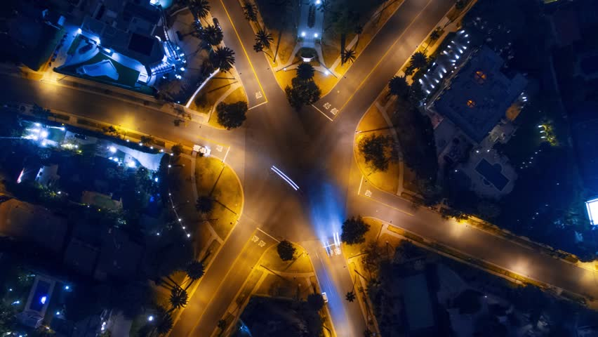Hyperlapse timelapse of night city traffic on 6-way stop street intersection circle roundabout in Beverly Hills, CA. 4K UHD vertical aerial view. | Shutterstock HD Video #17248012