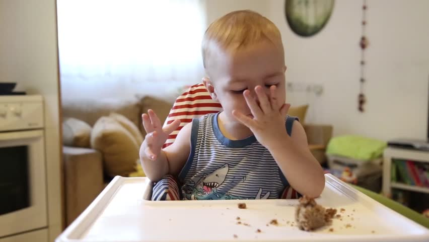 Toddler eating a cake with appetite. Baby.