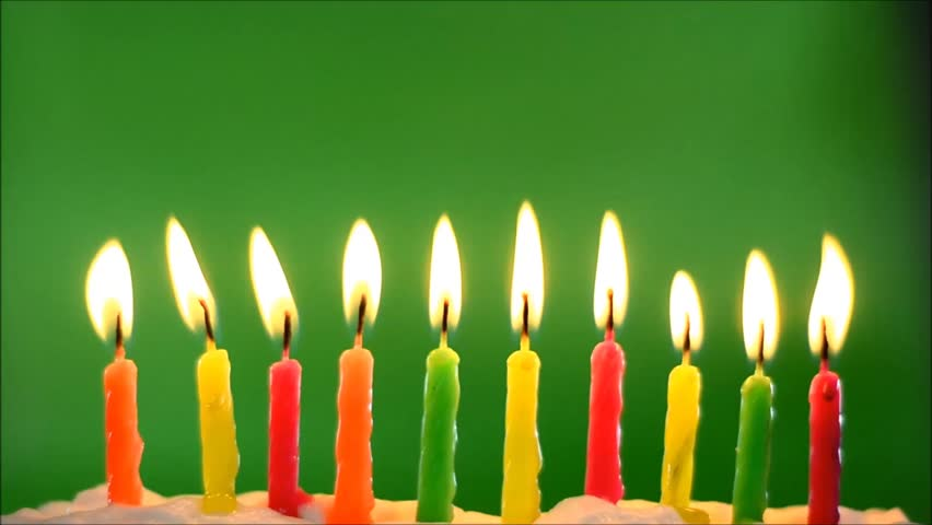 Ten multi-colored birthday candles in white icing in front of a green background flickering as melting wax trickles down the candles.