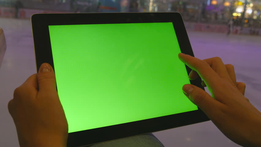 Female hands using tablet pc with green screen in shopping mall. Lot of people skate on indoor ice rink at the background | Shutterstock HD Video #17379259