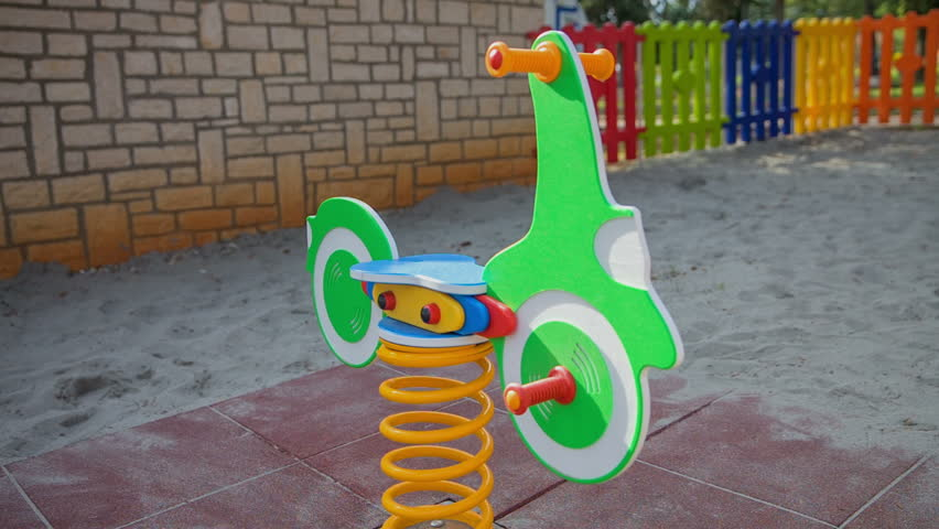 Green wooden pony is standing in the playground and it is ready for the children to use it. Close-up shot. - HD stock video clip