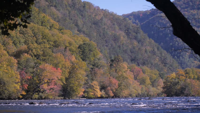 Tilt down of the French Broad River in Hot Spring, NC in autumn showing the changing leaves of fall. - HD stock footage clip