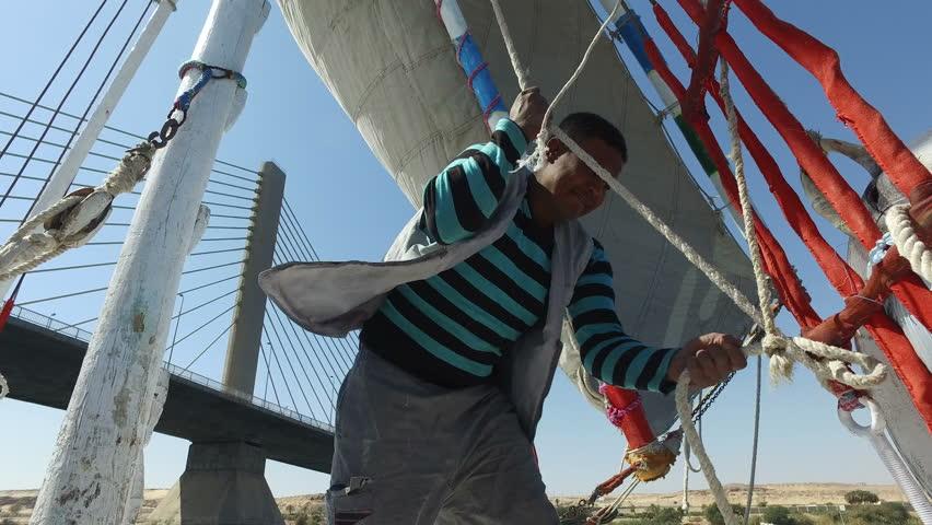 NILE, EGYPT - FEBRUARY 8, 2016: Nubian felucca sailing crew man on the Nile river - 4K stock footage clip