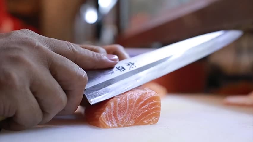 Sushi Chef Slices fresh Salmon on the sushi bar.A sushi-man slicing a salmon steak with his Japanese knife. Preparing sushi nigiri fish. Japanese cuisine recipes.