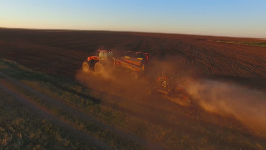 Aerial view tractor working in the vast field
