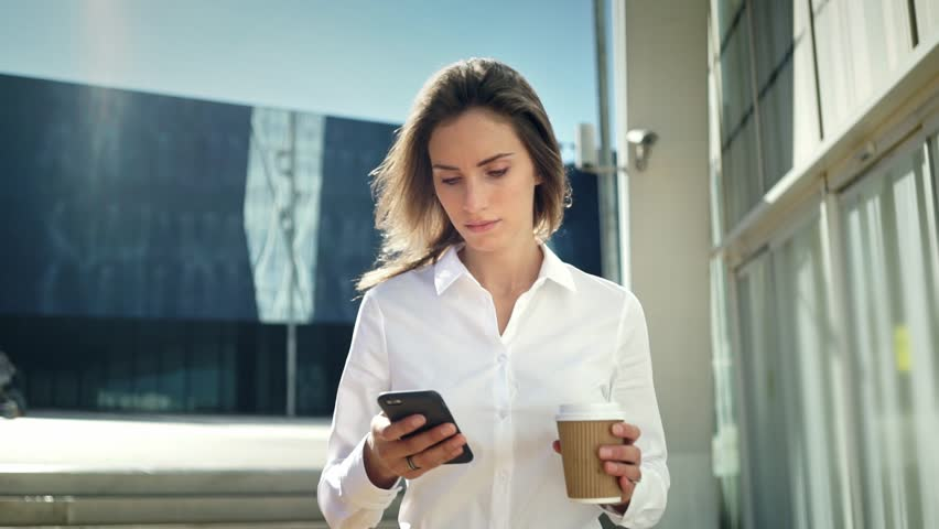 Beautiful young businesswoman wearing white shirt and using modern smart phone while walking at break in the city, professional female employer typing text message on cellphone outside, slow motion  | Shutterstock HD Video #17524690