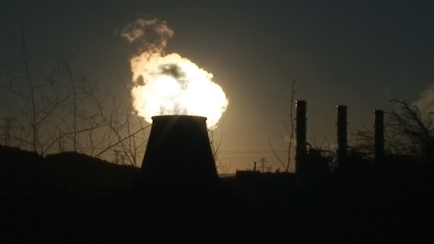 Chimney of power plant against sun, cooling towers emitting much pollution - HD stock footage clip