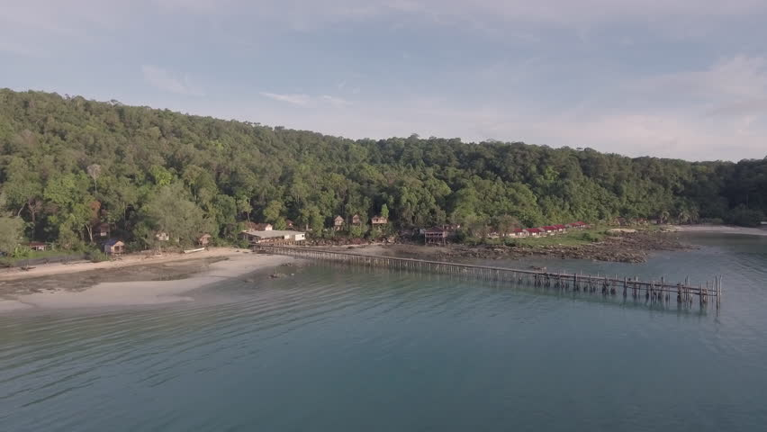 Aerial drone shot - wooden pier on the white  beach and bungalows at the foot of a tropical rain forest in the background | Shutterstock HD Video #17607499