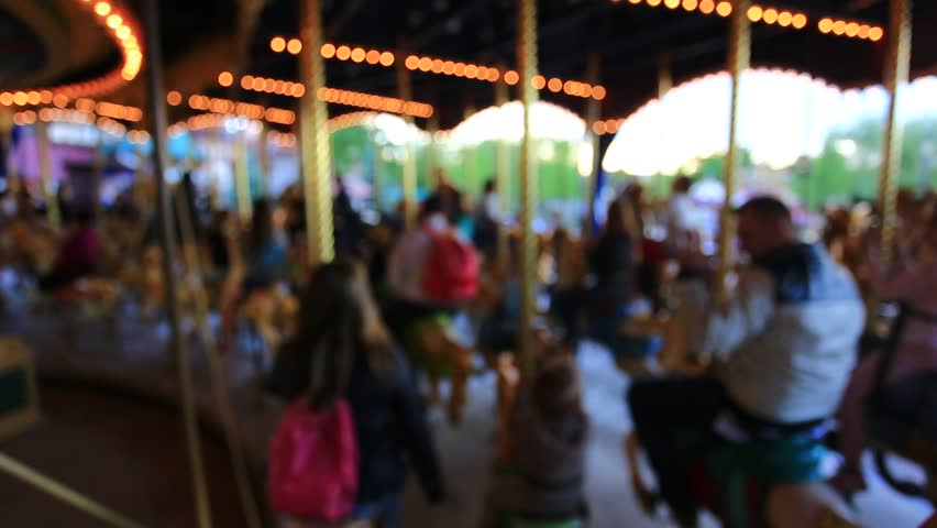family play on carousel moving,taking blurred motion of moving slow. - HD stock video clip