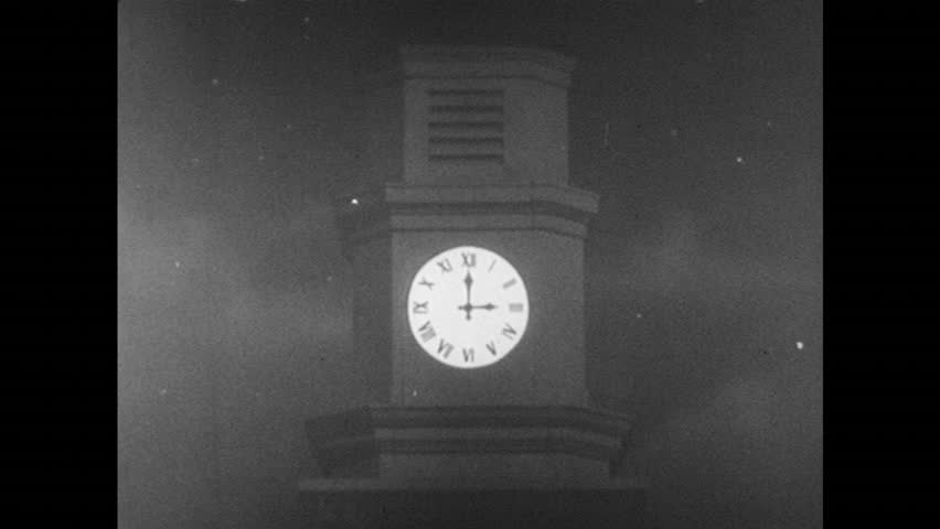 UNITED STATES 1950s: View of clock tower / Dissolve, baby in crib, hand pulls up blanket  / View of street at night / Long shot of town / Soldier next to window / Soldiers walk down stairs  - HD stock footage clip