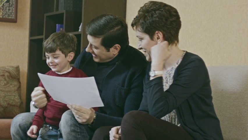 Happy family. Little boy showing his painting to his parents. Parents hug to their son. Shot on RED EPIC Cinema Camera in slow motion. - HD stock footage clip