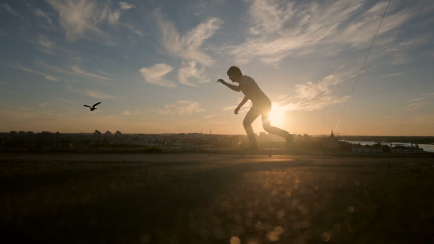 Young skaters training in the park in sunset. Birds. - HD stock footage clip