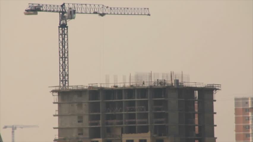 Tower crane near monolith cement building