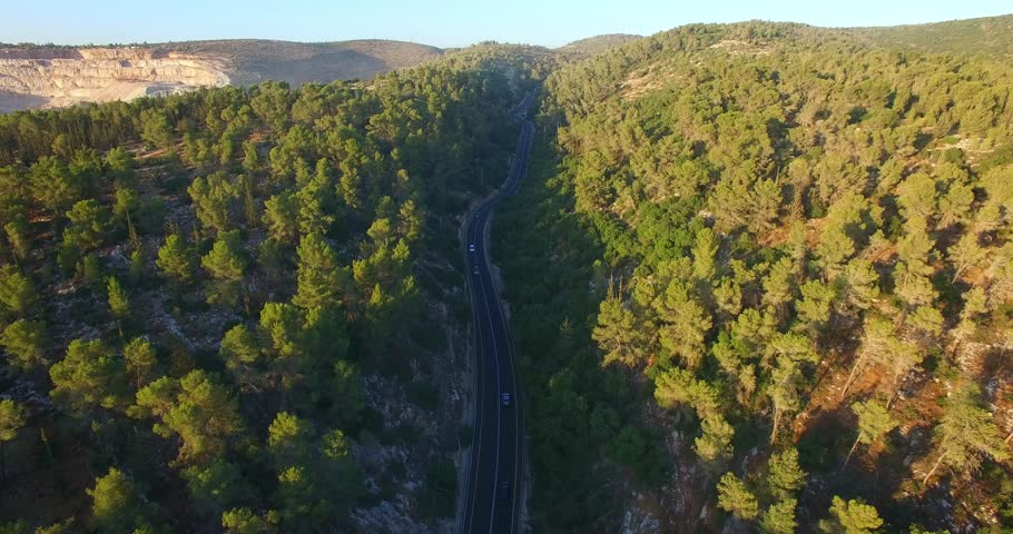 Aerial Road through mountains. Forest road.