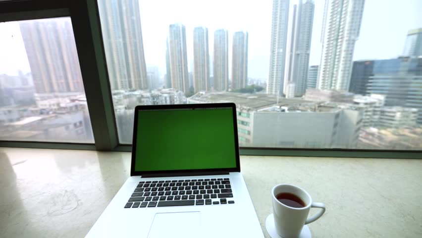Pretty workspace with laptop, morning cup of coffee and amazing view of skyscrapers from the high window. Hong Kong, China. | Shutterstock HD Video #17837152