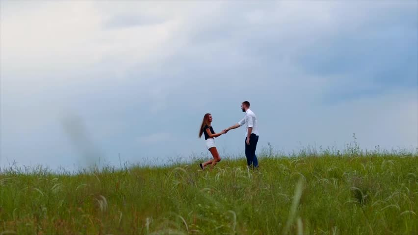 Young couple walking through green field - HD stock footage clip