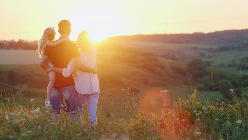 Happy family of three meet the dawn sun - HD stock footage clip