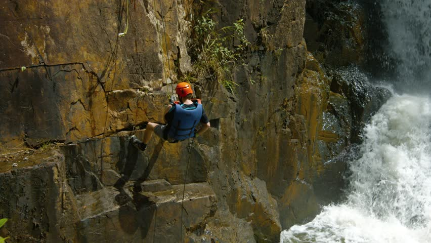 DA LAT. VIETNAM - CIRCA JAN 2016: Adventurous tourist rappels into the river beneath Datanla Falls near Da Lat. 4k UltraHD video - 4K stock footage clip