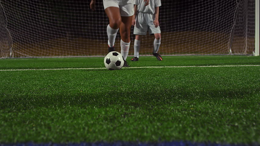 A female soccer player dribbles down the field during a game at night, in real time - 4K stock footage clip