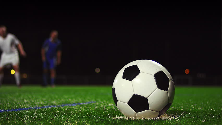 Close up of a soccer ball being kicked in slow motion at night, in real time - 4K stock video clip