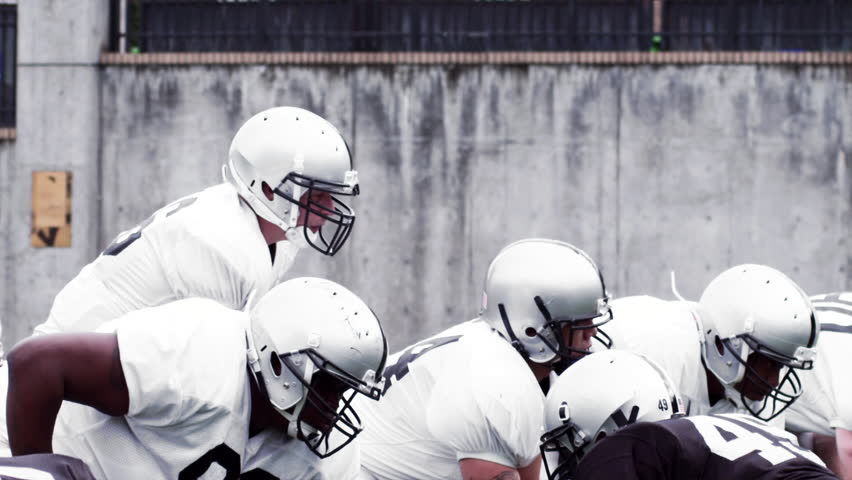 A Football team protects the Quarterback as he passes the ball. Slow motion. - HD stock footage clip