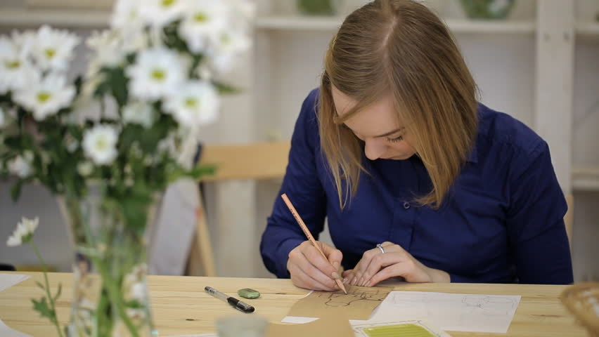 Blonde woman creates sketch on thick piece of cardboard in workshop. - HD stock footage clip