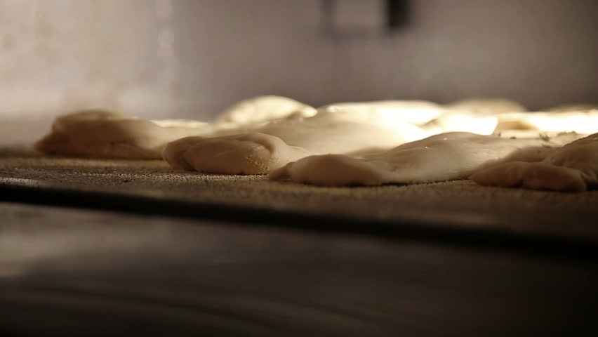Baker puts raw bread into the bakery