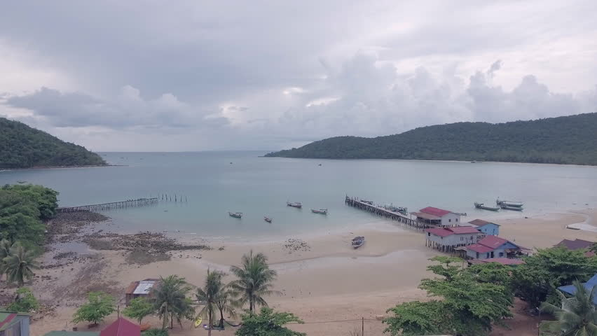 Aerial drone shot: Low flying panning right to fishing village and fishing boats docked at the wooden pier on a tropical beach under cloudy skies