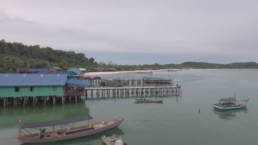 Cambodia - august - 2016:  low flying towards and over fishing boats docked at the wooden piers and fishing village. Fisherman fishing pole one of the pier