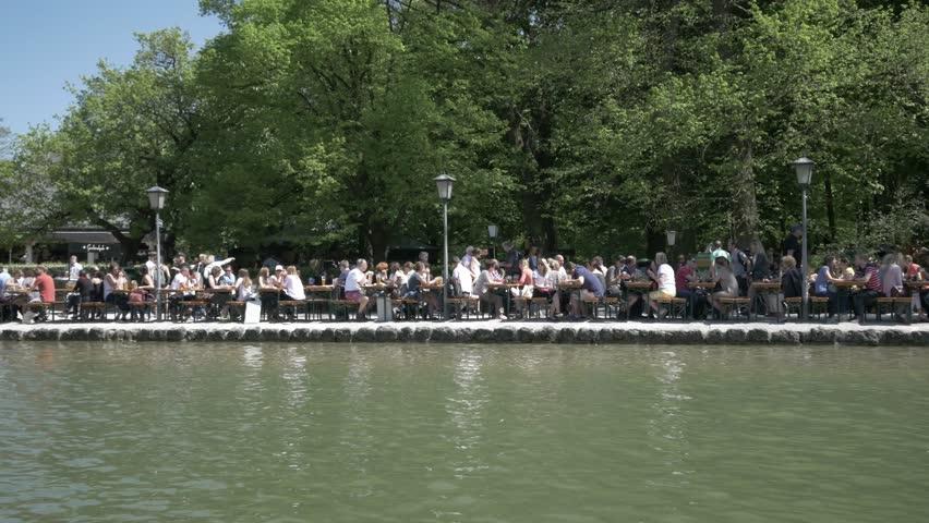 MUNICH, GERMANY - JUNE 03 2016:  The Englischer Garten in Munich, Bavaria, people people enjoy the sun. - 4K stock footage clip