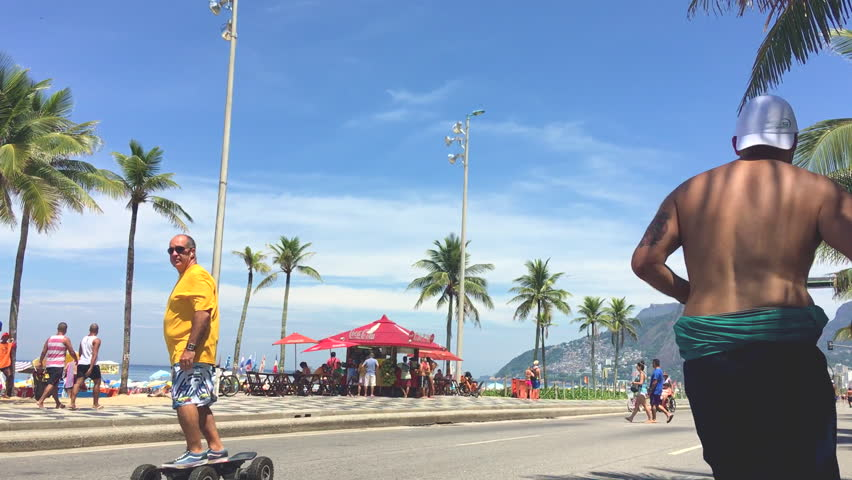 RIO DE JANEIRO - FEBRUARY 28, 2016: Brazilian man with a remote control skateboard passes along the beachfront road Avenida Vieira Souto in Ipanema Beach, which is closed to vehicles on Sundays.  - HD stock video clip