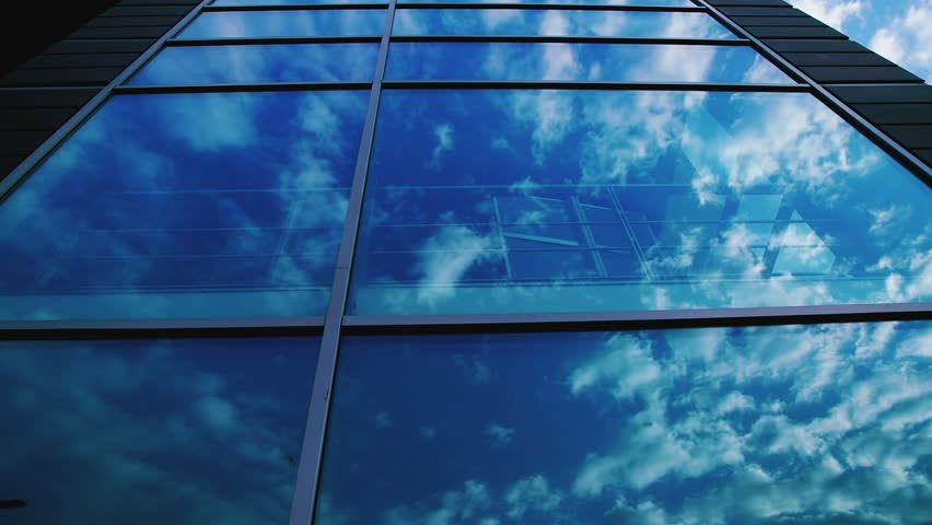 High Building and Windows with Reflection of Blue Sky and Clouds at Day - HD stock video clip