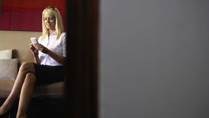 Female caucasian manager texting with mobile phone in hotel room during business trip. Dolly shot