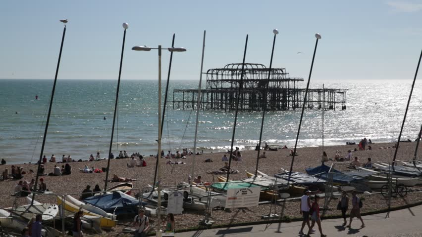 Ocean: Brighton Beach and Burned west pier - through the masts of boats, England - HD stock footage clip