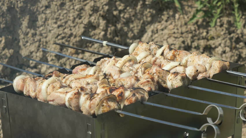 Frying of marinated meat on metal skewers on coals