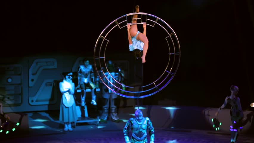 """ST. PETERSBURG, RUSSIA - JANUARY 2, 2016: Brothers Zapashny circus, """"UFO. Alien Planet Circus"""" show in Saint Petersburg. Alien spins a big wheel on his head where woman gymnast does tricks"""