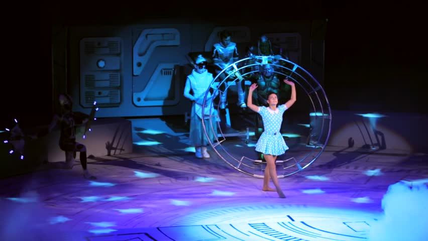 """ST. PETERSBURG, RUSSIA - JANUARY 2, 2016: Brothers Zapashny circus, """"UFO. Alien Planet Circus"""" show in Saint Petersburg. Woman gymnast in the middle of the stage, aliens dance around her."""